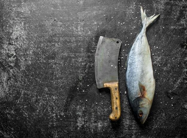 Peixe cru com uma grande faca na mesa rústica escura