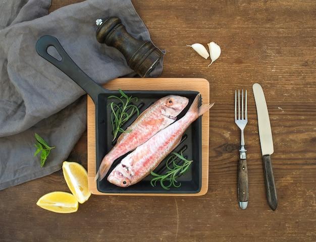 Peixe cru cru salmonete em uma panela com alecrim, limão e alho