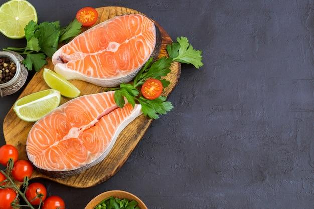 Peixe cru de bife de salmão preparado para cozinhar. vista superior na mesa preta.