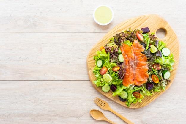 Peixe cru de carne de salmão defumado com salada de legumes verde fresca