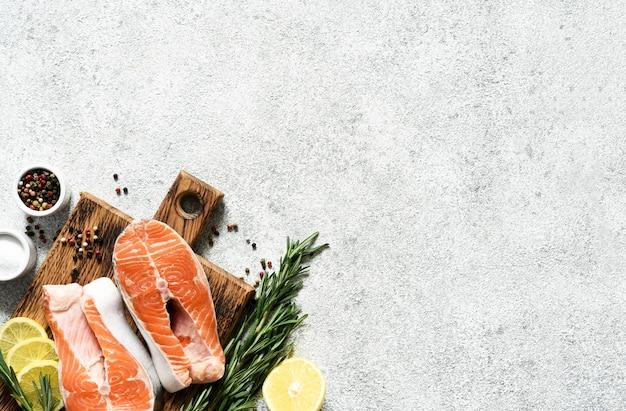 Peixe cru de filé de salmão com especiarias preparadas para cozinhar. vista superior sobre fundo claro e concreto.