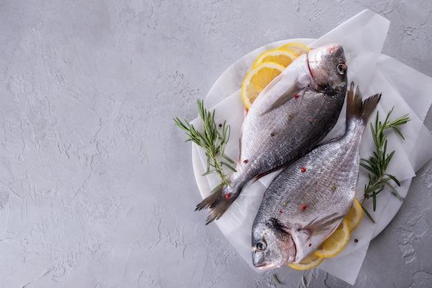 Peixe cru delicioso dorado ou pargo com especiarias de limão, alecrim fresco na placa de mármore vista de cima