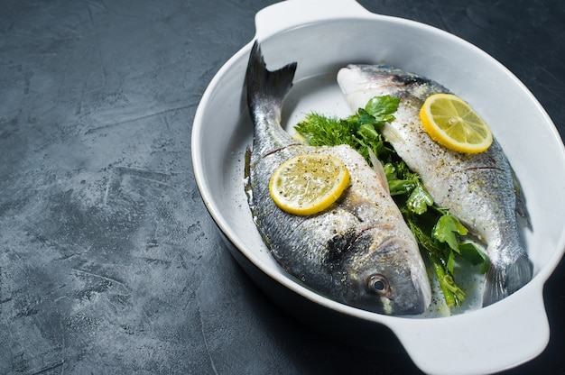Peixe cru dorado marinado em azeite, sal e pimenta, uma fatia de limão por cima.