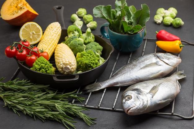 Peixe cru e frigideira com legumes na grelha. caneca com folhas verdes.
