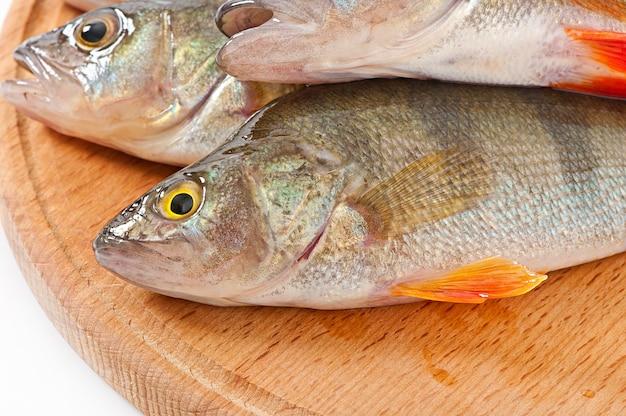 Peixe cru em uma placa de corte isolada