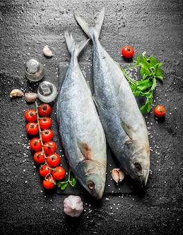 Peixe cru em uma tábua de pedra com tomate, salsa e especiarias na mesa rústica preta