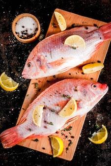Peixe cru fresco rosa tilápia com especiarias para cozinhar - limão, sal, pimenta, ervas