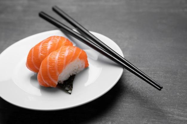 Peixe cru no prato com palitos de alto ângulo