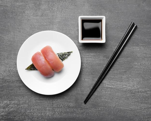 Peixe cru no prato com palitos e molho de soja