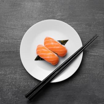 Peixe cru no prato com palitos vista de cima