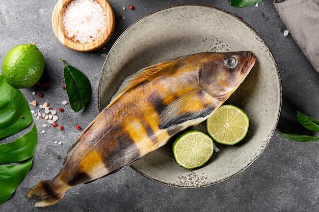 Peixe cru ou lingcod e temperos para cozinhá-lo em um plano de fundo cinza vista superior close-up