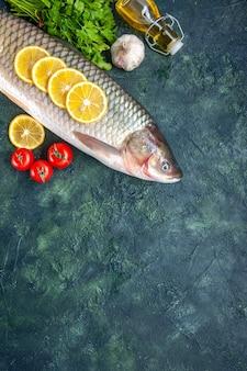 Peixe cru, tomate, fatias de limão, garrafa de óleo na mesa com espaço livre