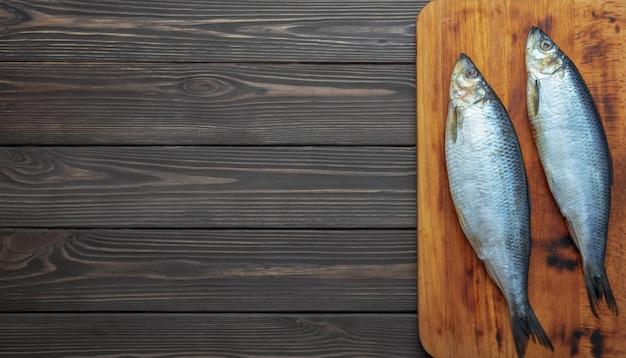 Peixe de arenque atlântico em conserva em uma tábua de corte