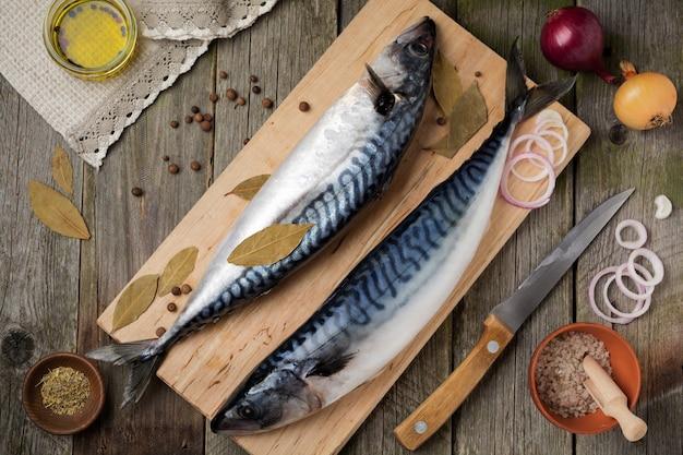 Peixe de cavala crua com ingredientes em um fundo de madeira velho