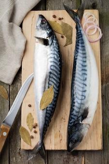 Peixe de cavala crua com ingredientes para cozinhar em um fundo de madeira velho estilo rústico. .