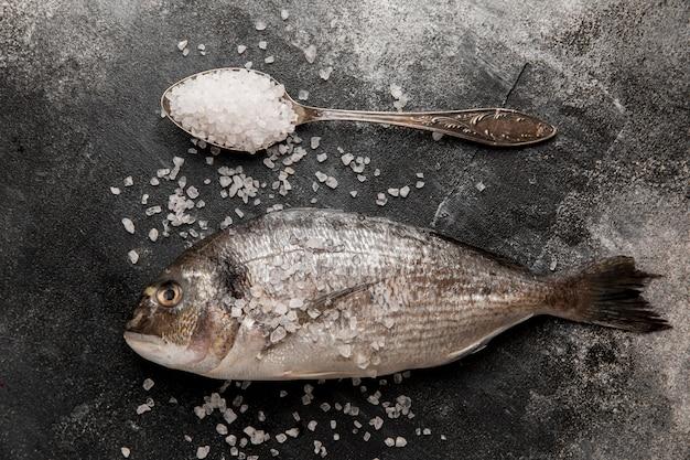 Peixe de marisco cru e colher com sal marinho