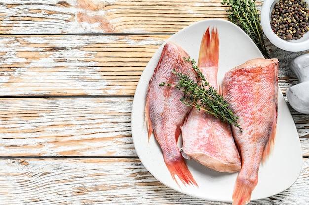 Peixe de pargo inteiro cru em um prato. mesa de madeira branca. vista do topo.