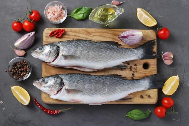 Peixe de robalo cru com ingredientes e temperos como manjericão, limão, sal, pimenta, tomate cereja e alho na placa de madeira
