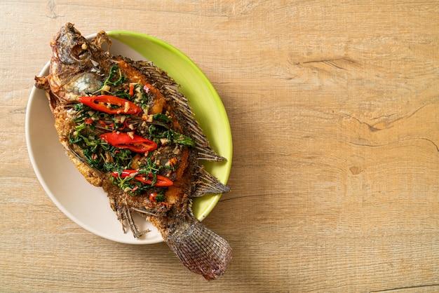 Peixe de tilápia frito com molho de manjericão e pimenta e alho por cima - estilo de comida caseira