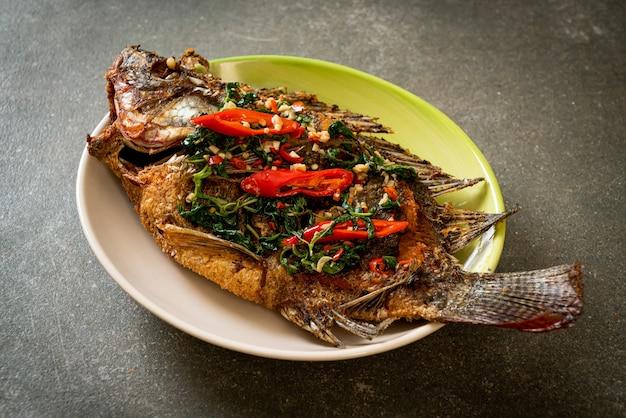 Peixe de tilápia frito com molho de manjericão e pimenta e alho por cima