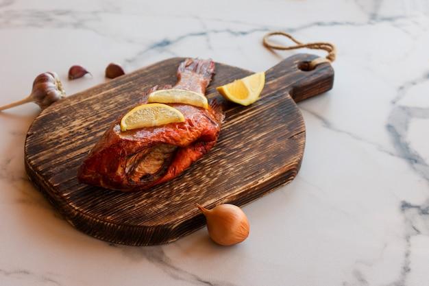 Peixe defumado delicioso oceano poleiro na tábua de madeira para alimentos saudáveis, dieta ou conceito de culinária, foco seletivo.