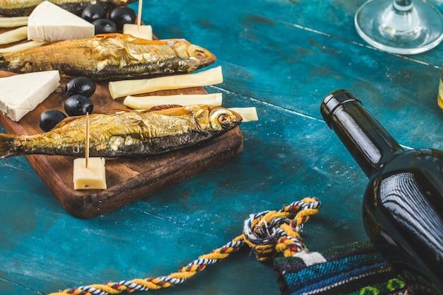 Peixe defumado, fatias de queijo e uma garrafa de vinho