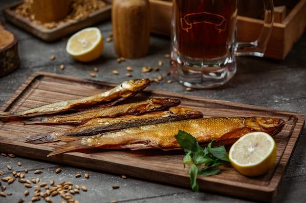 Peixe defumado seco servido com limão na placa de madeira para a noite de cerveja