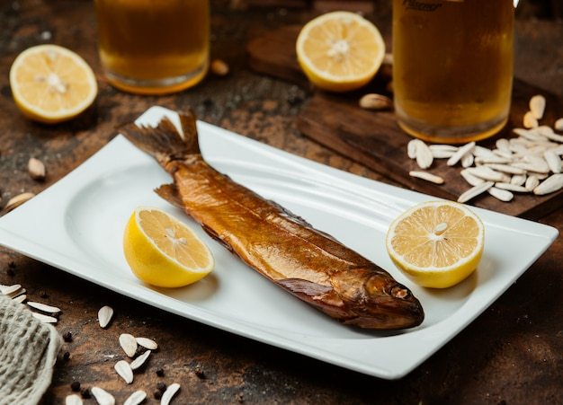 Peixe defumado seco servido com metades de limão, sementes de girassol salgadas e cerveja