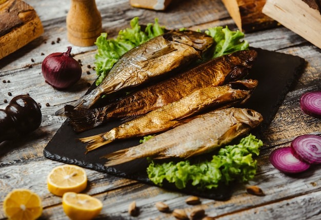 Peixe defumado servido no tabuleiro preto
