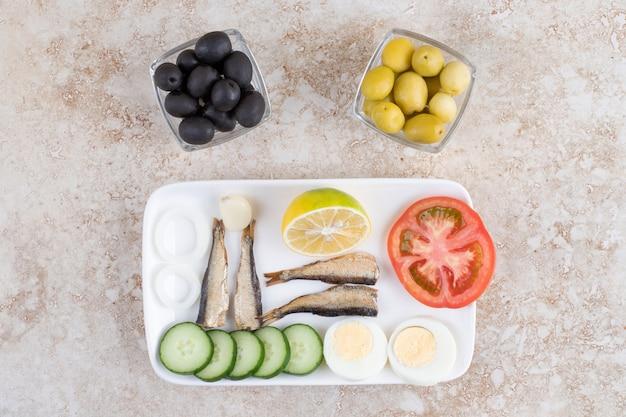 Peixe defumado, vegetais e ovos no prato branco