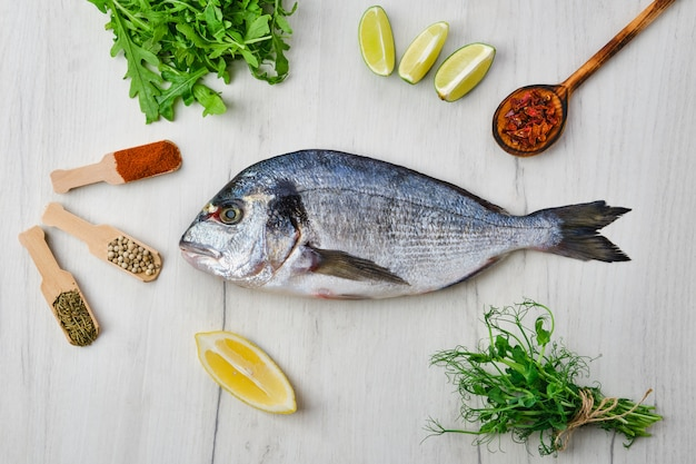 Peixe dorada em cima da mesa com especiarias e ervas