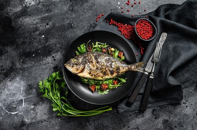 Peixe dorado grelhado com rúcula salada e tomate. fundo preto. vista do topo