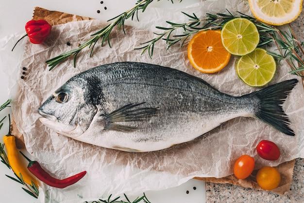 Peixe dourada dourada na assadeira com alecrim, limão, laranja, tomate, pimenta e limão