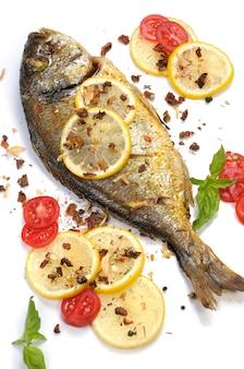 Peixe dourado assado com rodelas de limão e temperos com tomate