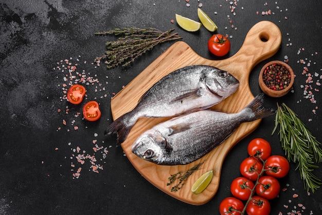 Peixe dourado cru com especiarias cozinhando na tábua. dorado de peixe fresco. dorado e ingredientes para cozinhar na mesa