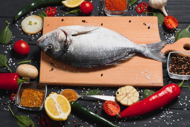 Peixe dourado cru fresco no papel manteiga com limão, pimenta, tomate e várias especiarias em fundo de madeira com espaço de cópia.