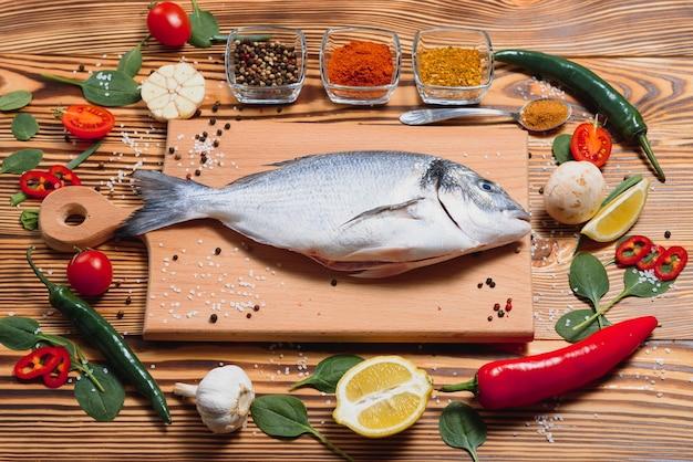 Peixe dourado cru fresco no papel manteiga com limão, pimenta, tomate e várias especiarias na superfície de madeira com espaço de cópia.