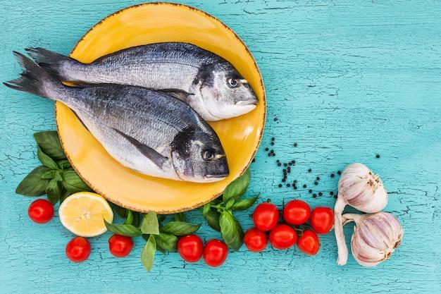 Peixe dourado cru na placa amarela, tomate, manjericão, alho e limão na mesa azul. vista superior, cópia