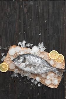 Peixe dourado cru ou dourada no gelo com rodelas de limão e alecrim sobre fundo preto de madeira, vista plana, vista de cima.