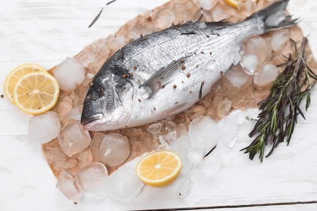 Peixe dourado cru ou dourada no gelo com rodelas de limão e alecrim sobre superfície de madeira branca, planta plana, vista de cima.