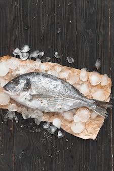 Peixe dourado cru ou dourada no gelo com rodelas de limão e alecrim sobre superfície de madeira preta, planta plana, vista de cima.