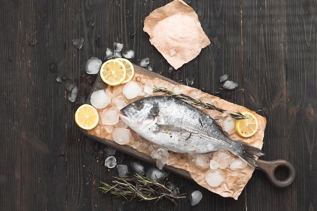 Peixe dourado cru ou dourada no gelo com rodelas de limão, sal e alecrim sobre fundo preto de madeira, vista plana, vista de cima.