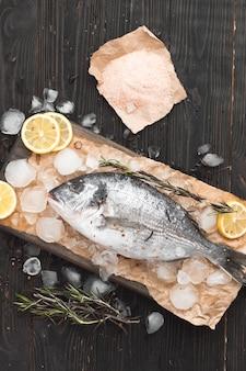 Peixe dourado cru ou dourada no gelo com rodelas de limão, sal e alecrim sobre superfície de madeira preta, planta plana, vista de cima.