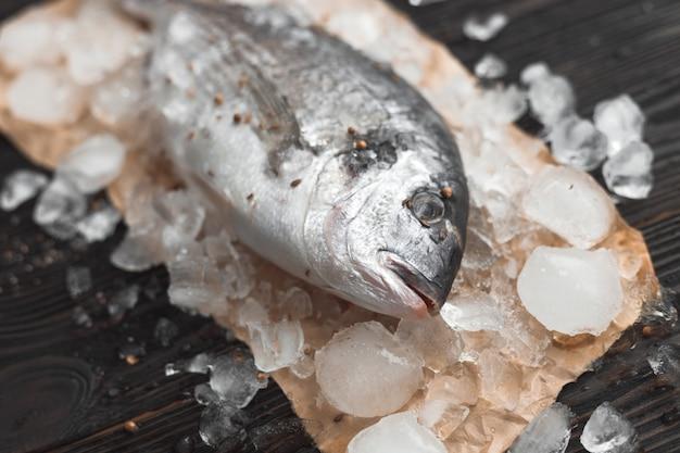 Peixe dourado cru ou dourada no gelo sobre uma superfície de madeira preta.