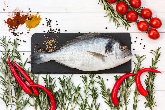 Peixe dourado fresco, alecrim, tomate cereja, pimenta fria na mesa de madeira branca. vista do topo.