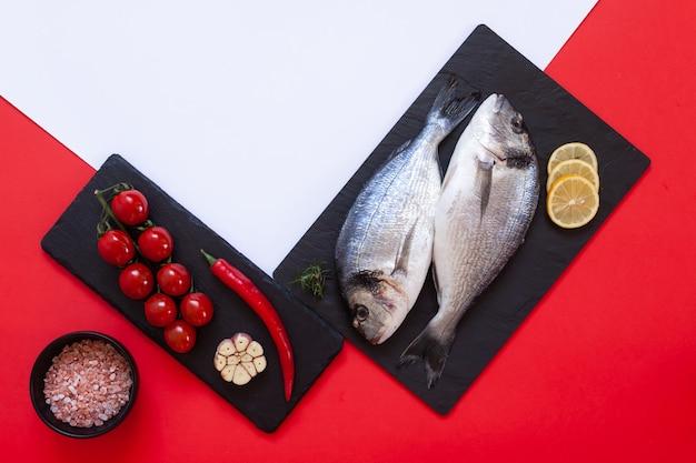 Peixe dourado fresco com especiarias, alho e temperos na tábua de corte preta