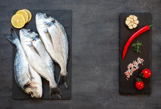 Peixe dourado fresco com especiarias, alho, limão e temperos na tábua preta sobre a mesa