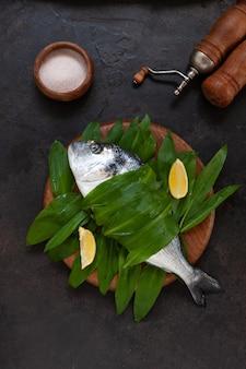 Peixe dourado fresco com folhas de alho selvagem, rodelas de limão e especiarias. vista superior, close-up, copie o espaço