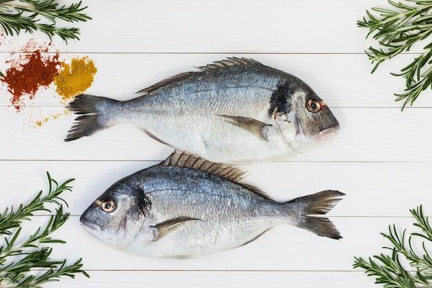 Peixe dourado fresco cru na mesa de madeira branca com alecrim. vista do topo