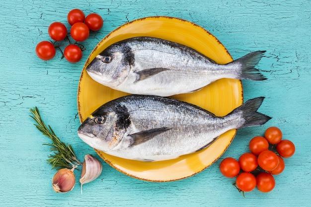 Peixe dourado fresco cru no prato e vegetais sobre fundo azul. vista do topo.